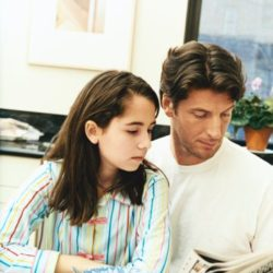 Father With His Daughter Sitting at a Kitchen Counter With Breakfast Cereal Reading a Newspaper